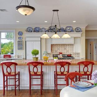 Große Maritime Wohnküche in L-Form mit Arbeitsplatte aus Holz, Elektrogeräten mit Frontblende, profilierten Schrankfronten, Kücheninsel, weißen Schränken, Küchenrückwand in Beige, Rückwand aus Keramikfliesen und braunem Holzboden in Seattle