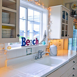 Design ideas for a small beach style galley separate kitchen in Seattle with an integrated sink, recessed-panel cabinets, white cabinets, tile benchtops, white splashback, white appliances, vinyl floors, no island and glass tile splashback.
