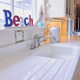 Photo of a small beach style galley separate kitchen in Seattle with an integrated sink, white cabinets, tile benchtops, white splashback, white appliances, vinyl floors, no island, glass tile splashback and recessed-panel cabinets.