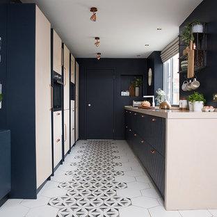 他の地域の小さいコンテンポラリースタイルのおしゃれなII型キッチン (フラットパネル扉のキャビネット、ベージュのキャビネット、マルチカラーの床、ベージュのキッチンカウンター、セラミックタイルの床、アイランドなし) の写真