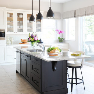 Large traditional l-shaped eat-in kitchen in Vancouver with an undermount sink, shaker cabinets, white cabinets, granite benchtops, white splashback, glass tile splashback, stainless steel appliances, porcelain floors and with island.