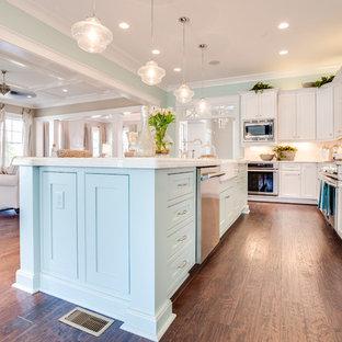 他の地域の大きいビーチスタイルのおしゃれなキッチン (エプロンフロントシンク、シェーカースタイル扉のキャビネット、白いキャビネット、クオーツストーンカウンター、白いキッチンパネル、石タイルのキッチンパネル、シルバーの調理設備の、濃色無垢フローリング) の写真