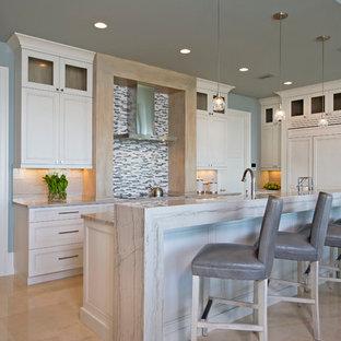 Inredning av ett maritimt mellanstort linjärt kök och matrum, med luckor med infälld panel, vita skåp, vitt stänkskydd, stänkskydd i stickkakel, integrerade vitvaror, marmorbänkskiva, marmorgolv, en köksö och beiget golv