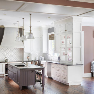 Traditional open concept kitchen ideas - Elegant l-shaped medium tone wood floor and brown floor open concept kitchen photo in Chicago with glass-front cabinets, white backsplash, white cabinets, an island, a farmhouse sink, granite countertops, ceramic backsplash and paneled appliances