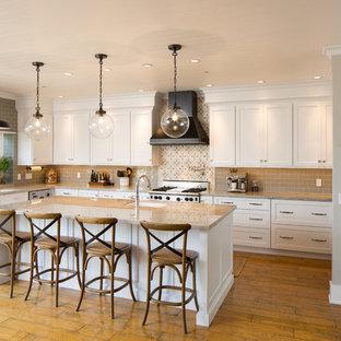 Große Klassische Wohnküche in U-Form mit Unterbauwaschbecken, Schrankfronten im Shaker-Stil, weißen Schränken, Quarzit-Arbeitsplatte, Küchenrückwand in Beige, Rückwand aus Glasfliesen, Küchengeräten aus Edelstahl, braunem Holzboden, Kücheninsel und braunem Boden in San Luis Obispo