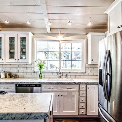 Mid-sized arts and crafts l-shaped dark wood floor and brown floor open concept kitchen photo in San Diego with an undermount sink, shaker cabinets, white cabinets, granite countertops, white backsplash, subway tile backsplash, stainless steel appliances and an island