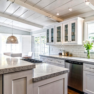 Design ideas for a medium sized classic l-shaped open plan kitchen in San Diego with a submerged sink, shaker cabinets, white cabinets, granite worktops, white splashback, metro tiled splashback, stainless steel appliances, dark hardwood flooring, an island and brown floors.