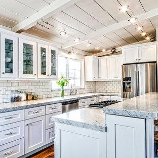 Exempel på ett mellanstort amerikanskt kök, med en undermonterad diskho, skåp i shakerstil, vita skåp, granitbänkskiva, vitt stänkskydd, stänkskydd i tunnelbanekakel, rostfria vitvaror, mörkt trägolv, en köksö och brunt golv