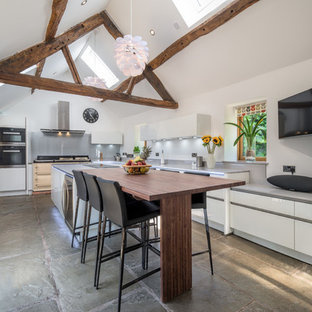 This is an example of a large rustic kitchen in Other with flat-panel cabinets, white cabinets, grey splashback, an island, grey floors and grey worktops.