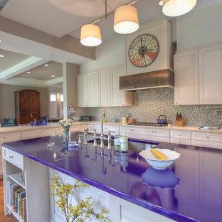 Foto på ett stort funkis lila kök, med en dubbel diskho, skåp i shakerstil, bänkskiva i kvarts, flerfärgad stänkskydd, vita skåp, integrerade vitvaror, en köksö, mellanmörkt trägolv och brunt golv
