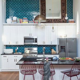 ニューヨークの中サイズのエクレクティックスタイルのおしゃれなキッチン (アンダーカウンターシンク、シェーカースタイル扉のキャビネット、白いキャビネット、シルバーの調理設備の、青いキッチンパネル、サブウェイタイルのキッチンパネル、無垢フローリング) の写真