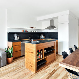Photo of a small scandinavian l-shaped open plan kitchen in New York with flat-panel cabinets, medium wood cabinets, black splashback, stainless steel appliances, light hardwood flooring and an island.