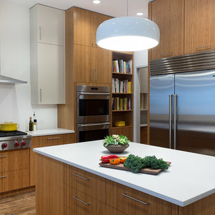 Mid-sized contemporary kitchen designs - Kitchen - mid-sized contemporary medium tone wood floor kitchen idea in New York with flat-panel cabinets, medium tone wood cabinets, quartz countertops, white backsplash, stainless steel appliances and an island