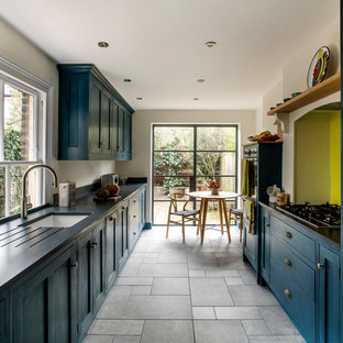Design ideas for a traditional kitchen in London with a belfast sink, shaker cabinets, blue cabinets, granite worktops, yellow splashback, glass sheet splashback, ceramic flooring and black worktops.