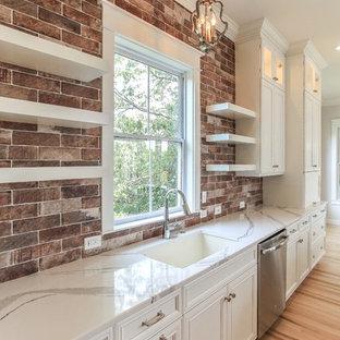 チャールストンのトランジショナルスタイルのおしゃれなアイランドキッチン (レイズドパネル扉のキャビネット、白いキャビネット、珪岩カウンター、マルチカラーのキッチンパネル、レンガのキッチンパネル、シルバーの調理設備の、淡色無垢フローリング) の写真