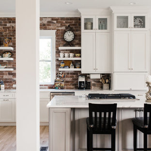 Mid-sized transitional u-shaped eat-in kitchen in Charleston with white cabinets, brick splashback, with island, an undermount sink, shaker cabinets, quartz benchtops, red splashback, stainless steel appliances, light hardwood floors, beige floor and white benchtop.
