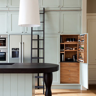 Photo of a victorian galley kitchen in London with an integrated sink, shaker cabinets, stainless steel appliances, medium hardwood floors, with island and blue cabinets.