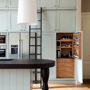 ロンドンのヴィクトリアン調のおしゃれなキッチン (一体型シンク、シェーカースタイル扉のキャビネット、シルバーの調理設備の、無垢フローリング、青いキャビネット) の写真