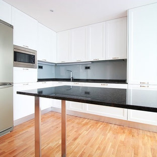 This is an example of a medium sized classic kitchen/diner in Madrid with a submerged sink, recessed-panel cabinets, white cabinets, granite worktops, grey splashback, glass tiled splashback, plywood flooring and an island.