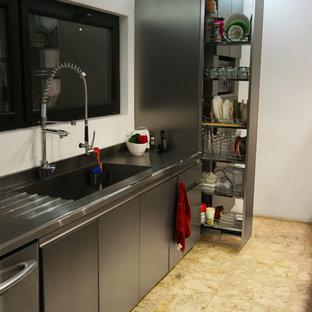 Foto de cocina comedor bohemia con fregadero integrado, armarios con paneles lisos, puertas de armario en acero inoxidable, encimera de acero inoxidable, electrodomésticos de acero inoxidable, suelo de terrazo y península