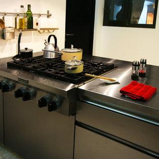 Modelo de cocina comedor bohemia con fregadero integrado, armarios con paneles lisos, puertas de armario en acero inoxidable, encimera de acero inoxidable, electrodomésticos de acero inoxidable, suelo de terrazo y península