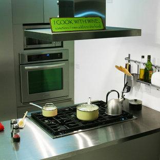 他の地域のエクレクティックスタイルのおしゃれなキッチン (一体型シンク、フラットパネル扉のキャビネット、ステンレスキャビネット、ステンレスカウンター、シルバーの調理設備の、テラゾの床) の写真