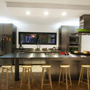 Imagen de cocina comedor ecléctica con fregadero integrado, armarios con paneles lisos, puertas de armario en acero inoxidable, encimera de acero inoxidable, electrodomésticos de acero inoxidable, suelo de terrazo y península