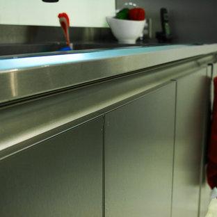 Ejemplo de cocina comedor ecléctica con fregadero integrado, armarios con paneles lisos, puertas de armario en acero inoxidable, encimera de acero inoxidable, electrodomésticos de acero inoxidable, suelo de terrazo y península