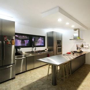 Imagen de cocina comedor actual con fregadero integrado, armarios con paneles lisos, puertas de armario en acero inoxidable, encimera de acero inoxidable, electrodomésticos de acero inoxidable, suelo de terrazo y península