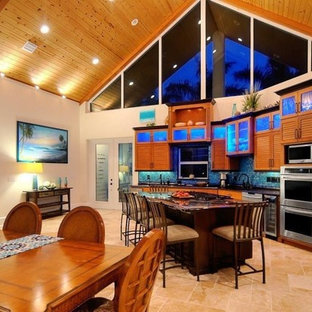 Photo of a mid-sized tropical u-shaped open plan kitchen in Orlando with an undermount sink, louvered cabinets, medium wood cabinets, granite benchtops, blue splashback, mosaic tile splashback, stainless steel appliances, limestone floors and with island.