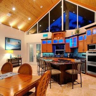 オーランドの中サイズのトロピカルスタイルのおしゃれなキッチン (アンダーカウンターシンク、ルーバー扉のキャビネット、中間色木目調キャビネット、御影石カウンター、青いキッチンパネル、モザイクタイルのキッチンパネル、シルバーの調理設備、ライムストーンの床) の写真