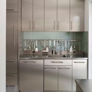 Inredning av ett modernt mellanstort kök, med en integrerad diskho, släta luckor, skåp i rostfritt stål, bänkskiva i rostfritt stål, glaspanel som stänkskydd, en köksö, rostfria vitvaror och betonggolv