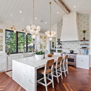 Inspiration för klassiska vitt kök, med en rustik diskho, skåp i shakerstil, vita skåp, marmorbänkskiva, flerfärgad stänkskydd, stänkskydd i cementkakel, rostfria vitvaror, mellanmörkt trägolv, en köksö och brunt golv