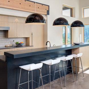 Immagine di una cucina abitabile design di medie dimensioni con ante lisce, ante in legno chiaro, top in cemento, paraspruzzi con piastrelle in ceramica, pavimento in cemento, isola, pavimento beige, paraspruzzi beige e elettrodomestici da incasso