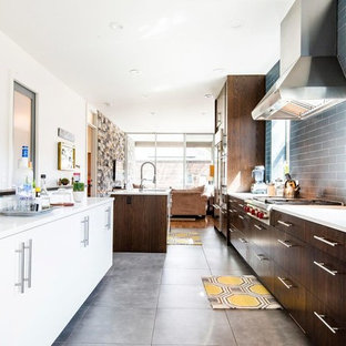 Photo of a mid-sized arts and crafts galley eat-in kitchen in Salt Lake City with a single-bowl sink, flat-panel cabinets, dark wood cabinets, limestone benchtops, blue splashback, ceramic splashback, stainless steel appliances, ceramic floors, with island, grey floor and white benchtop.