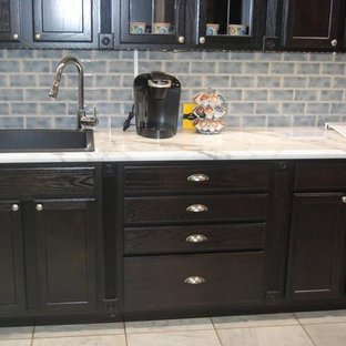Inspiration for a small transitional single-wall eat-in kitchen in Omaha with a drop-in sink, recessed-panel cabinets, dark wood cabinets, blue splashback, ceramic splashback, black appliances, porcelain floors and no island.