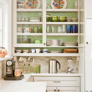 На фото: кухня в классическом стиле с стеклянными фасадами, белыми фасадами, бежевым фартуком и фартуком из травертина с