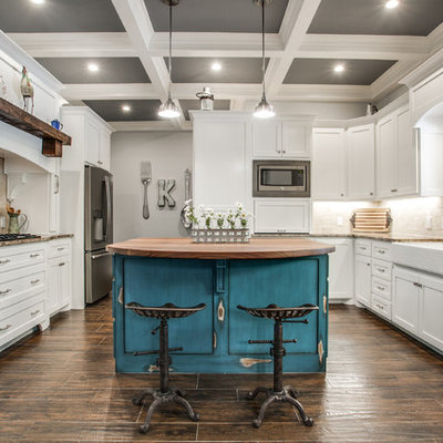 Mid-sized cottage u-shaped medium tone wood floor and brown floor kitchen photo in Dallas with a farmhouse sink, shaker cabinets, white cabinets, beige backsplash, stainless steel appliances, an island, granite countertops and stone tile backsplash