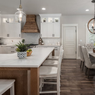 Mid-sized farmhouse eat-in kitchen ideas - Mid-sized farmhouse l-shaped medium tone wood floor eat-in kitchen photo in Salt Lake City with a drop-in sink, shaker cabinets, white cabinets, quartz countertops, white backsplash, stone tile backsplash, stainless steel appliances, an island and white countertops