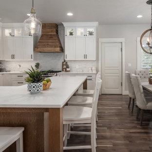 Bild på ett mellanstort lantligt vit vitt kök, med en nedsänkt diskho, skåp i shakerstil, vita skåp, bänkskiva i kvarts, vitt stänkskydd, stänkskydd i stenkakel, rostfria vitvaror, mellanmörkt trägolv och en köksö
