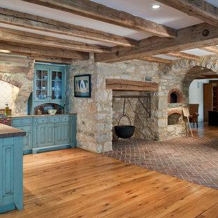 Inspiration pour une cuisine américaine chalet en L avec un électroménager en acier inoxydable, un placard avec porte à panneau surélevé, des portes de placard bleues, un plan de travail en bois, une crédence blanche, un évier encastré, une crédence en carreau de porcelaine, un sol en brique et un îlot central.