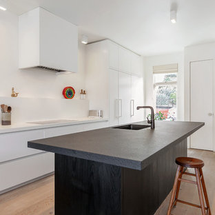 Inspiration for a large scandi galley kitchen in San Francisco with an integrated sink, flat-panel cabinets, white cabinets, granite worktops, white appliances, light hardwood flooring and an island.