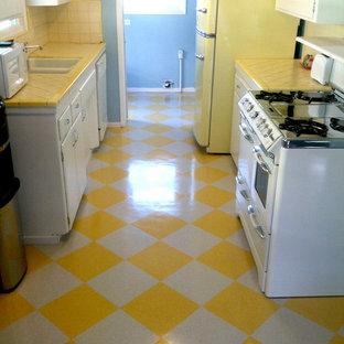 サンディエゴの小さいおしゃれなキッチン (ドロップインシンク、フラットパネル扉のキャビネット、白いキャビネット、タイルカウンター、黄色いキッチンパネル、セラミックタイルのキッチンパネル、カラー調理設備、クッションフロア、アイランドなし) の写真