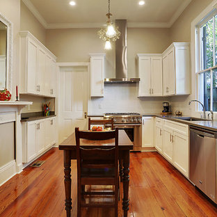 Medium sized classic u-shaped kitchen pantry in New Orleans with a submerged sink, shaker cabinets, white cabinets, engineered stone countertops, stainless steel appliances, medium hardwood flooring, no island, brown floors and grey worktops.