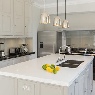 Inspiration for a medium sized classic u-shaped kitchen in Other with a double-bowl sink, recessed-panel cabinets, grey cabinets, glass sheet splashback, stainless steel appliances and an island.
