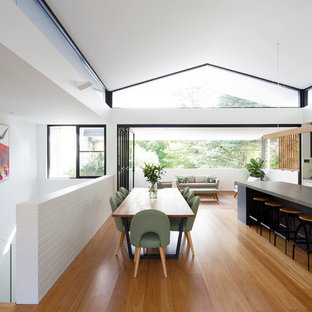 Inspiration for a mid-sized contemporary galley open plan kitchen in Sydney with an undermount sink, flat-panel cabinets, white cabinets, quartz benchtops, white splashback, glass sheet splashback, black appliances, medium hardwood floors, with island, brown floor and grey benchtop.