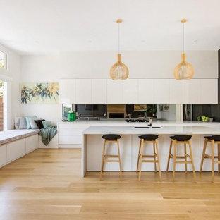 Idee per una cucina a L minimal con lavello sottopiano, ante lisce, ante bianche, paraspruzzi a specchio, elettrodomestici in acciaio inossidabile, parquet chiaro, isola, pavimento beige e top bianco