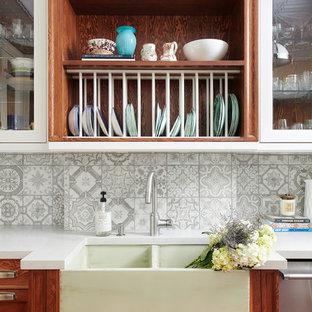 トロントの中サイズのエクレクティックスタイルのおしゃれなキッチン (エプロンフロントシンク、シェーカースタイル扉のキャビネット、中間色木目調キャビネット、人工大理石カウンター、グレーのキッチンパネル、セラミックタイルのキッチンパネル、シルバーの調理設備の、コンクリートの床、アイランドなし、赤い床、白いキッチンカウンター) の写真