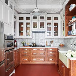 トロントの中サイズのエクレクティックスタイルのおしゃれなキッチン (エプロンフロントシンク、シェーカースタイル扉のキャビネット、中間色木目調キャビネット、グレーのキッチンパネル、セラミックタイルのキッチンパネル、シルバーの調理設備の、アイランドなし、赤い床、白いキッチンカウンター、人工大理石カウンター、コンクリートの床) の写真