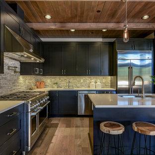 Diseño de cocina en L, rústica, con fregadero bajoencimera, armarios estilo shaker, puertas de armario negras, salpicadero verde, electrodomésticos de acero inoxidable, suelo de madera en tonos medios, una isla, suelo marrón y encimeras grises